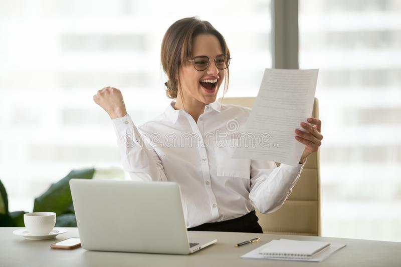 Excited employee reading letter with good news happy about promo. Excited satisfied businesswoman celebrating business success motivated by great financial work stock images