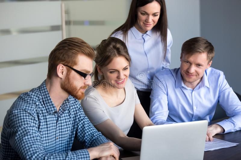Excited employees looking at laptop observing growing statistics stock photography