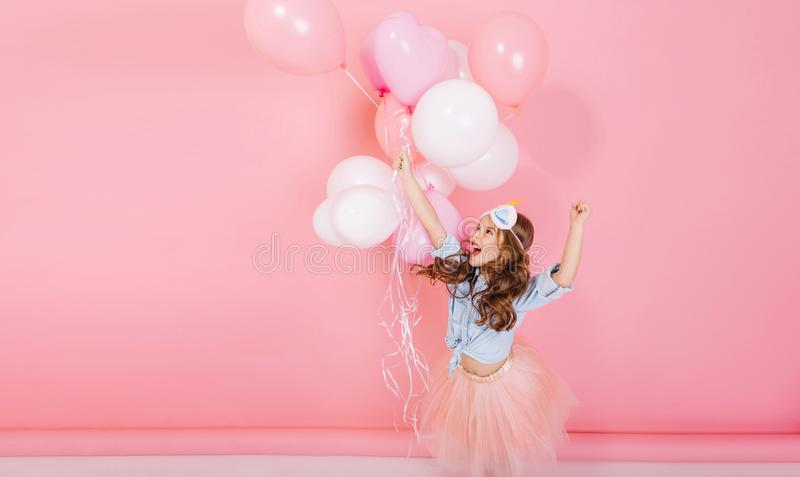 Excited entertainment of happy little girl in tulle skirt running with flying balloons isolated on pink background. Happy celebration of birthday party stock photos