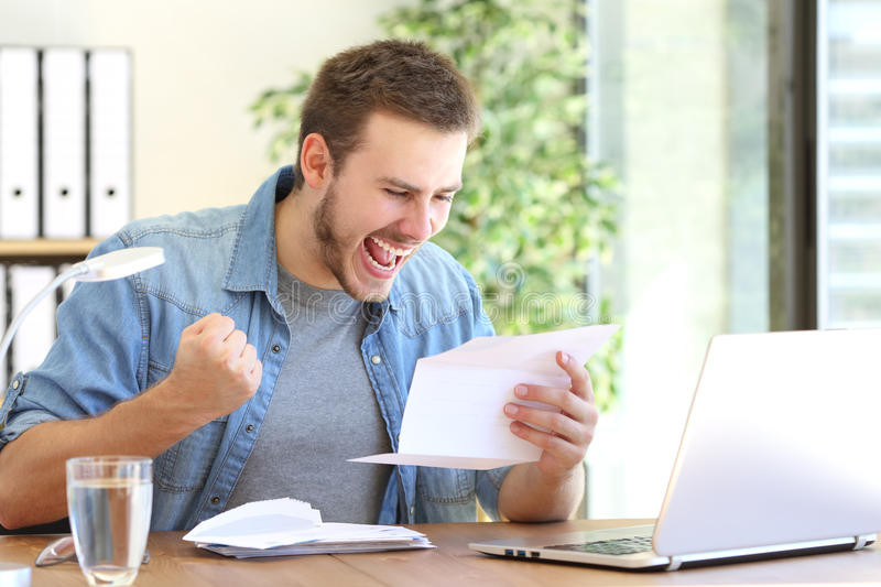 Excited entrepreneur reading a letter royalty free stock photo