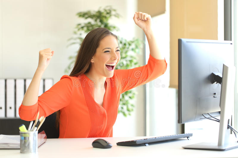 Excited entrepreneur watching computer monitor. Excited entrepreneur wearing an orange blouse reading good news on line in a desktop computer monitor in the royalty free stock photo