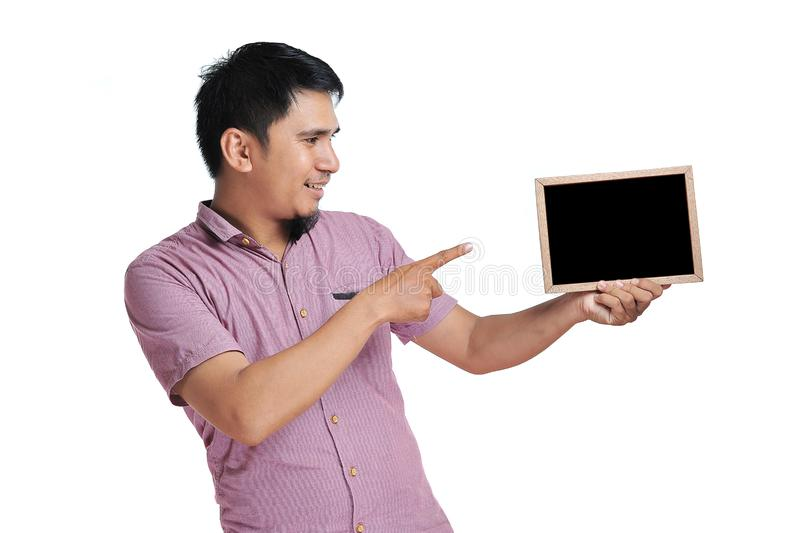 Excited expression of happy smiling asian man pointing the blackboard for copyspace stock photos