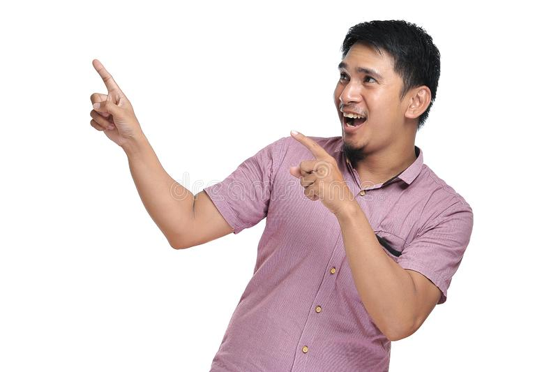 Excited expression of happy smiling asian man pointing of a copyspace royalty free stock photos