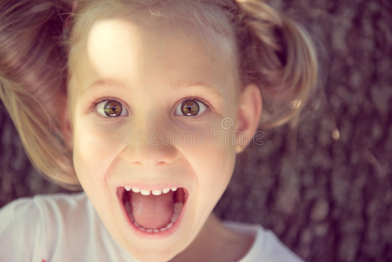 Excited face of pretty girl in summer park royalty free stock image
