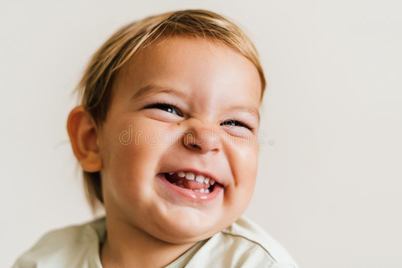 Excited face of a small baby toddler on white background. Pure joy. Close up portrait royalty free stock photography