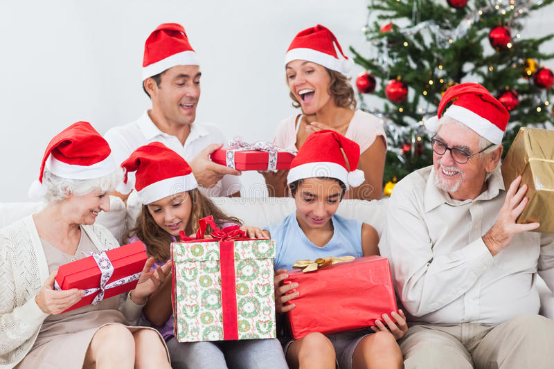 Excited family exchanging gifts at christmas stock photos