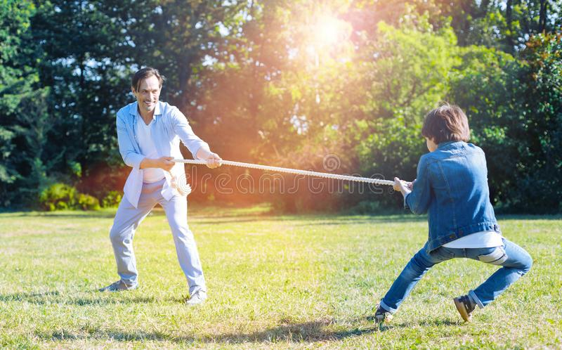 Excited father and son playing tug of war together royalty free stock image