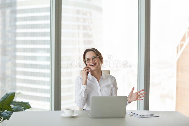 Smiling businesswoman happily talking over phone with friend royalty free stock photos