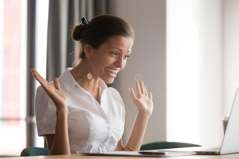 Excited female employee feel euphoric reading good news. Excited female employee sit at office desk feel euphoric look at laptop winning online lottery, happy royalty free stock image