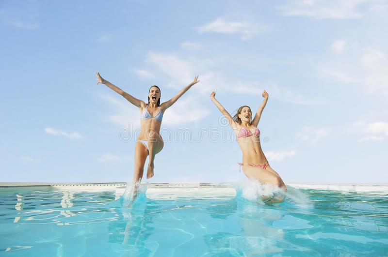 Excited Female Friends Jumping In Pool Stock Images