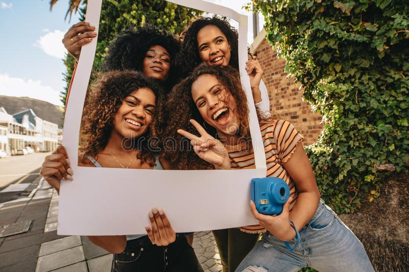 Excited friends with blank photo frame stock images