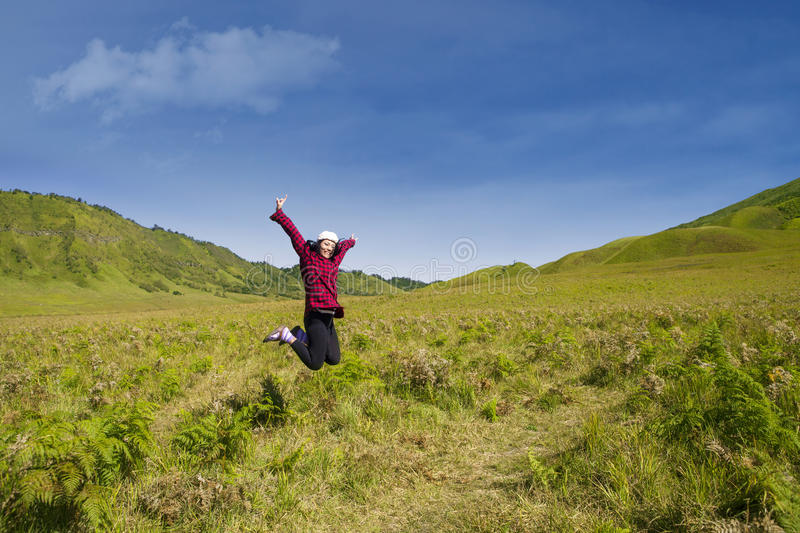 Download Excited Female Jumping In Grass Field Stock Photo - Image: 32582904