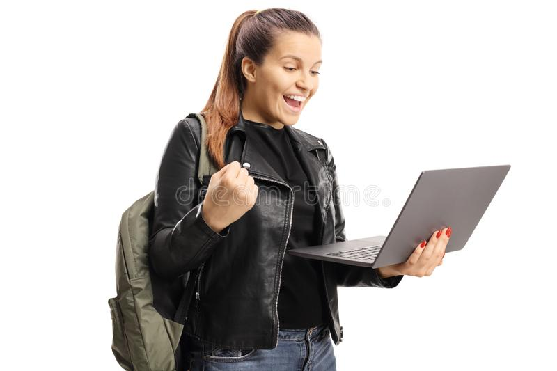 Excited female student gesturing and holding a laptop. Isolated on white background stock photo