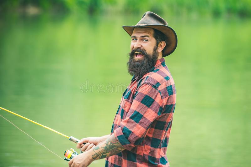 Excited fisher man fishing with spinning reel. Trout on a hook. Difference between fly fishing and regular fishing. stock photography
