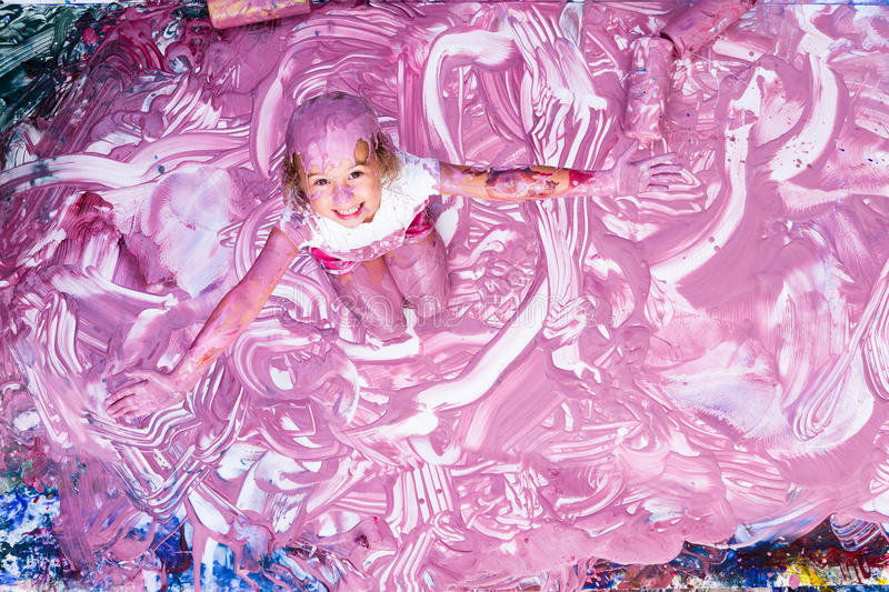 Excited five year old playing in paint stock image
