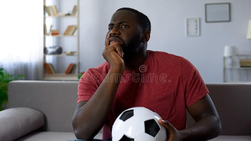 Excited football fan watching game home, unhappy with team failure in match. Stock photo royalty free stock image