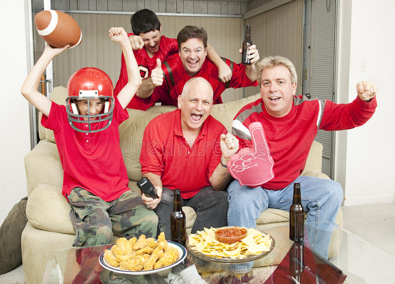 Excited Football Fans. Family of football fans cheering for their favorite team stock photo