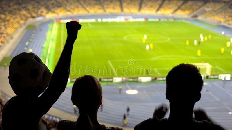 Excited football fans cheering team during soccer match at crowded stadium stock photos