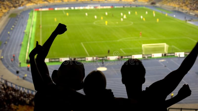 Excited football fans cheering team during soccer match at crowded stadium stock photography