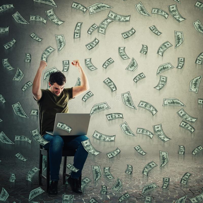 Excited freelancer guy seated working on laptop raising hands up holding fists as celebrating win. Money falling like dollar rain stock photo
