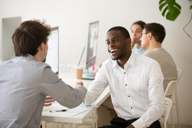 Excited friendly african manager handshaking customer or colleag. Friendly african advisor handshaking customer or colleague in office, smiling black and white stock image