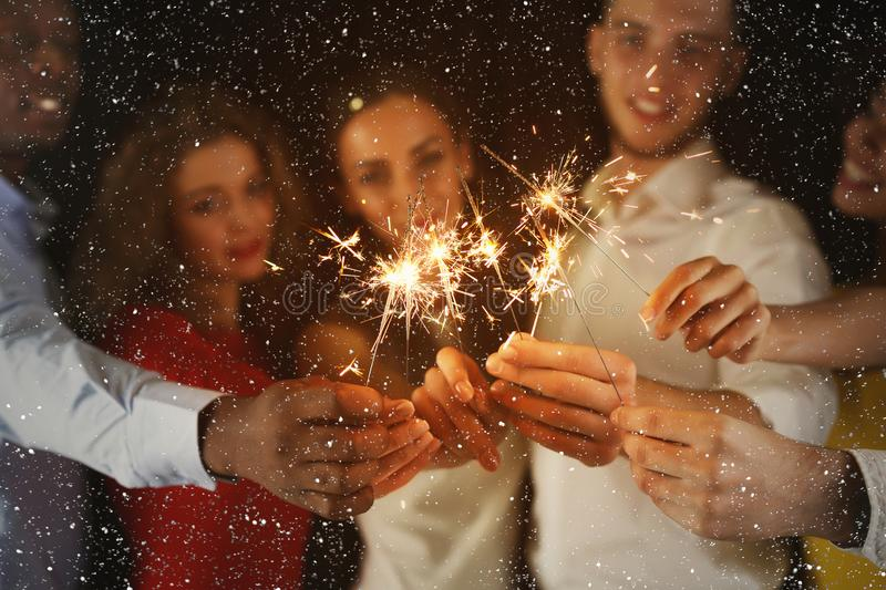 Excited friends holding bengal lights at New Year party royalty free stock images