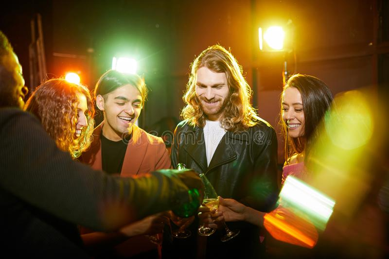 Excited friends pouring champagne in nightclub royalty free stock photo