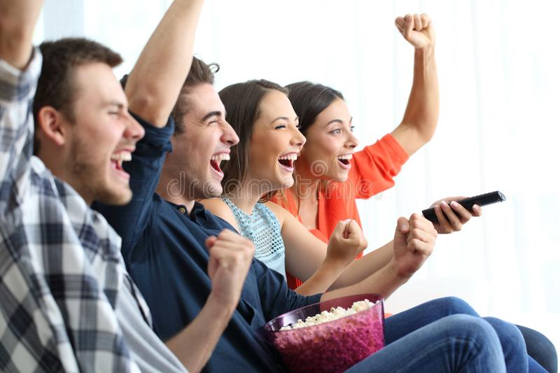 Excited friends watching tv celebrating success royalty free stock photos
