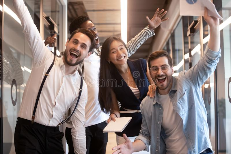 Excited funny multiethnic business team stand in office, portrait. Excited funny multiethnic staff people business team stand in office looking at camera, happy stock image