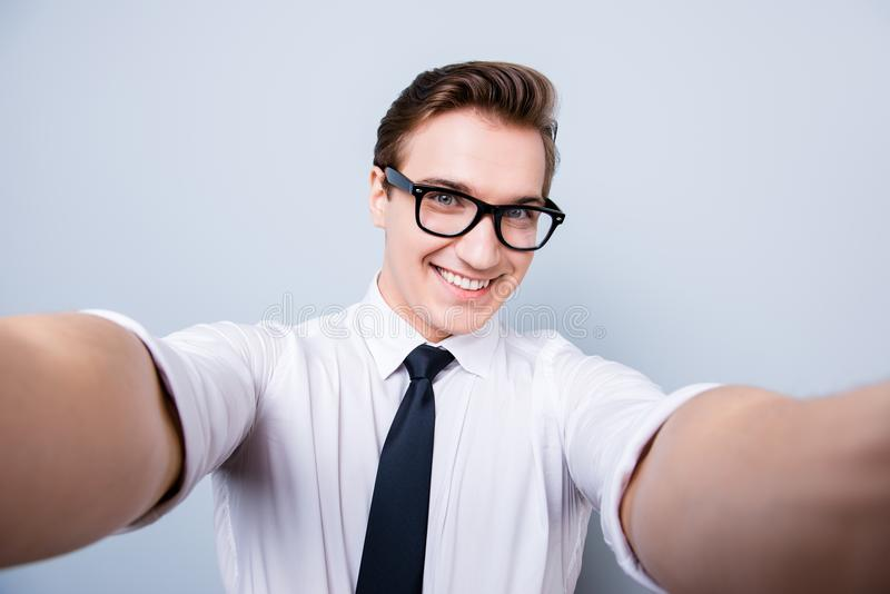Excited geek young man in trendy glasses and formal wear is making selfie shot on camera, standing on a pure background, showing stock image
