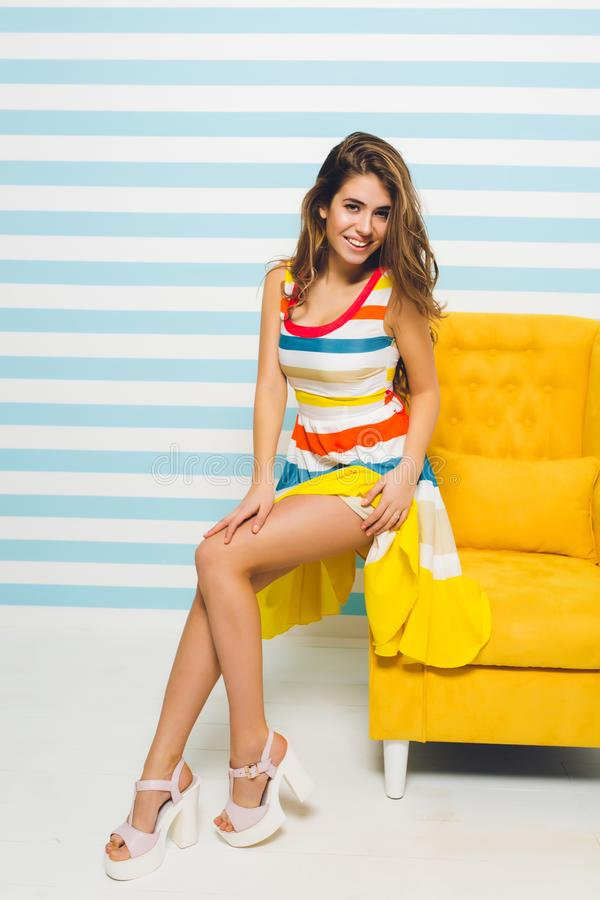 Excited girl with beautiful hairstyle looking away, sitting on modern yellow furniture on striped background. Portrait stock photo