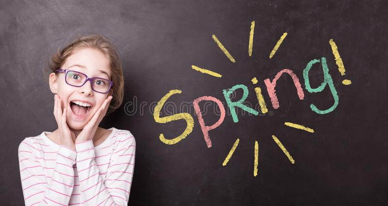 Excited girl at the chalkboard with colorful `Spring!` sign royalty free stock photography