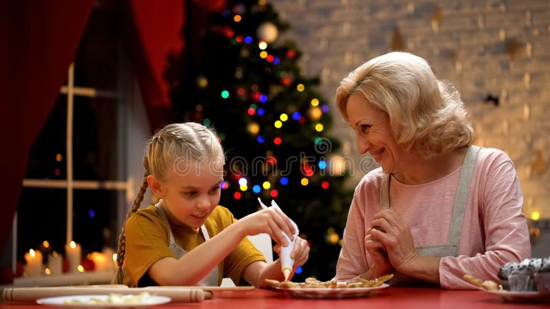Excited girl decorating Xmas cookies with granny, family festive traditions royalty free stock images
