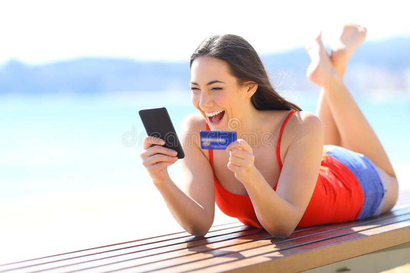 Excited girl finding ecommerce offers buying online. With phone and credit card on the beach royalty free stock images