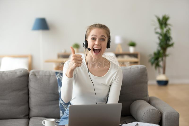 Excited girl in headset using laptop showing thumbs up. Portrait of excited young female wearing headset show thumbs up to camera recommending online course or royalty free stock image