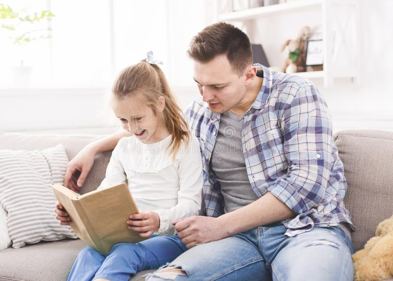 Excited girl and her father enjoying book together stock photography
