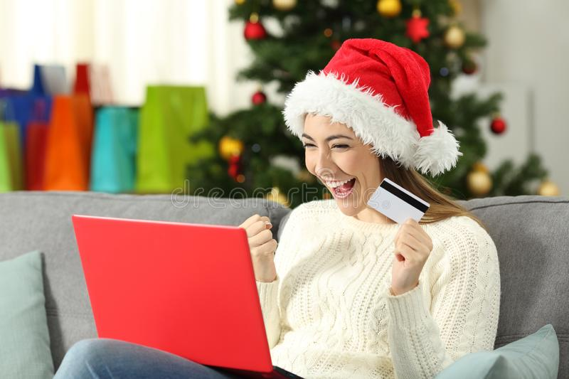 Excited girl holding a card shopping online on christmas. Sitting on a couch in the living room at home stock photography