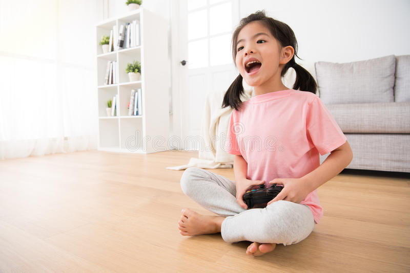 Excited girl kid playing video game at home stock images