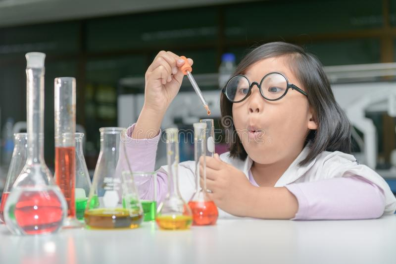 Excited girl making experiment with test tube royalty free stock photos