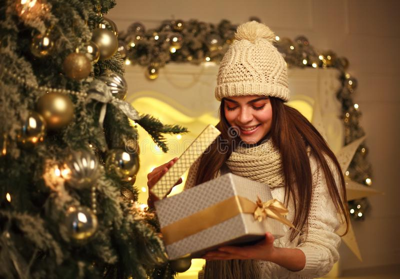 Excited girl opens Christmas gift at home in New Year`s decor. Joyful excited girl opens Christmas gift at home in New Year`s decor stock images