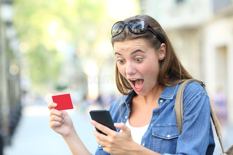 Excited girl paying with credit card and phone royalty free stock photo