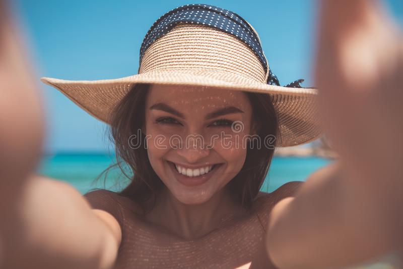 Excited girl taking photos on the beach stock photography
