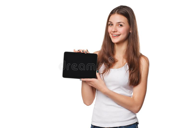 Excited girl in white shirt showing tablet pc monitor. Smiling woman with tablet pc, isolated on orange background royalty free stock images