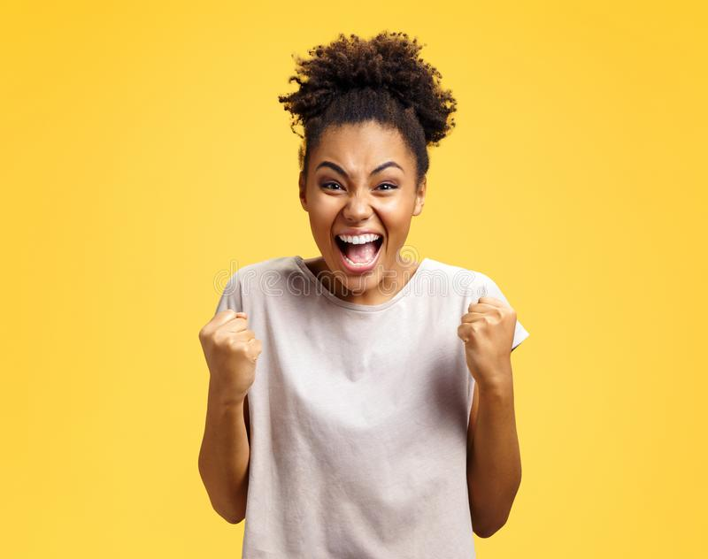 Excited girl with widely open mouth holds hands clenched in fists, exclaimed with positiveness. stock photo