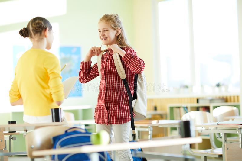 Excited girls discussing task in classroom. Positive excited schoolgirls in casual clothing discussing task in classroom, girl in yellow sweater asking question royalty free stock photography