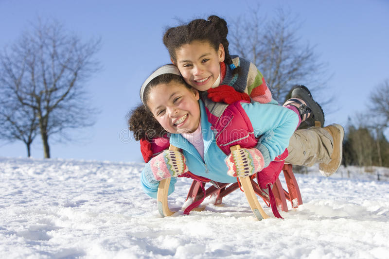 Excited girls sledding down snowy hill on sled stock photography