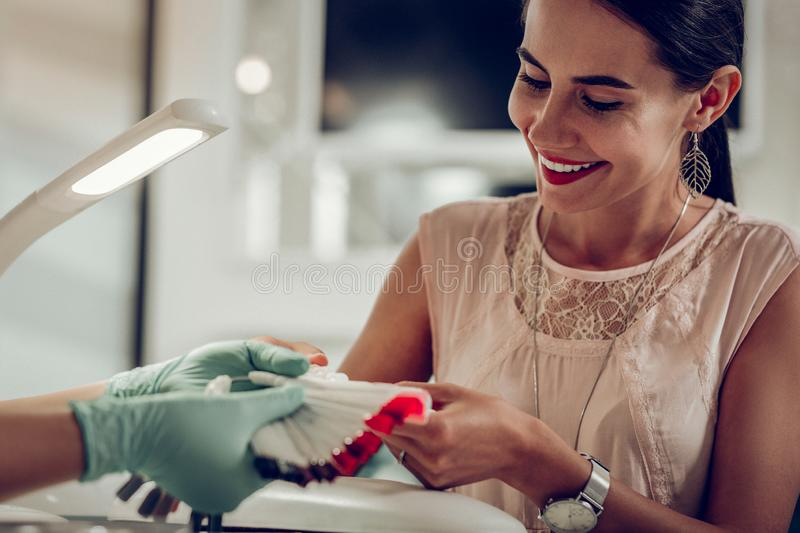 Excited good-looking woman with wide smile observing nail colors stock photos