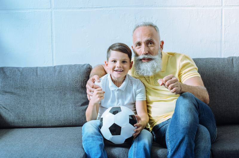 Excited grandchild and senior man watching football match stock photo