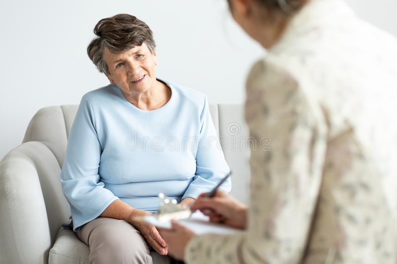 Excited grandmother talking to a psychologist about positive lif. E of pensioner royalty free stock images