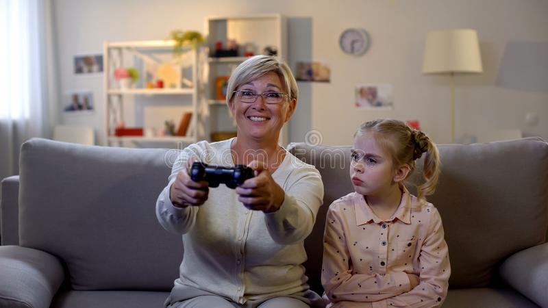 Excited granny playing video game ignoring sad grandchild sitting sofa addiction royalty free stock image